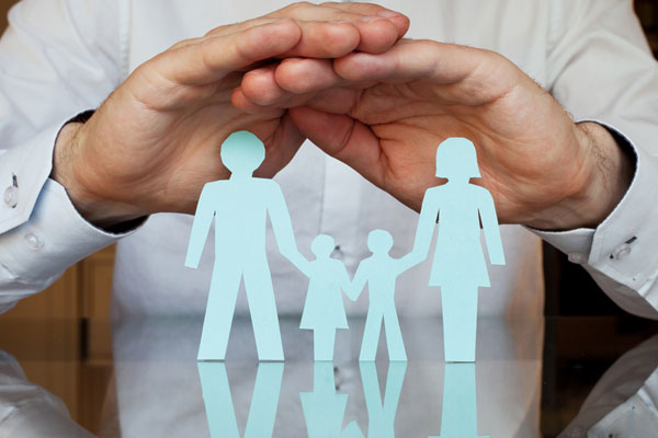Paper cut-out of family shielded by hands
